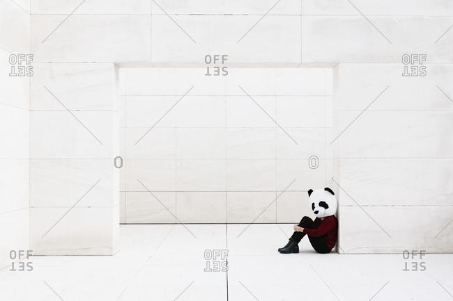Woman wearing panda mask sitting at doorway against white wall