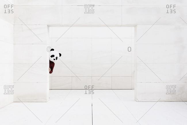 Man wearing panda mask hiding behind doorway