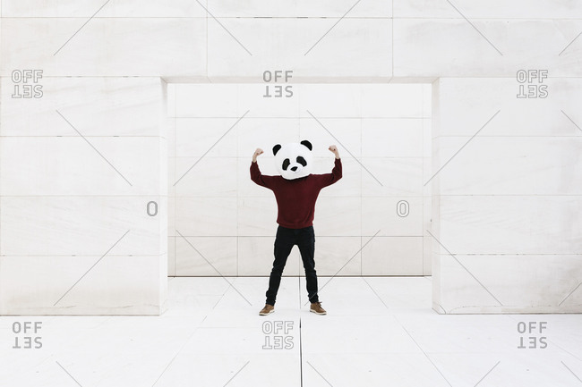 Man wearing panda mask flexing muscles while standing at doorway against white wall