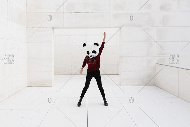 Woman wearing panda mask with hand raised while standing against doorway