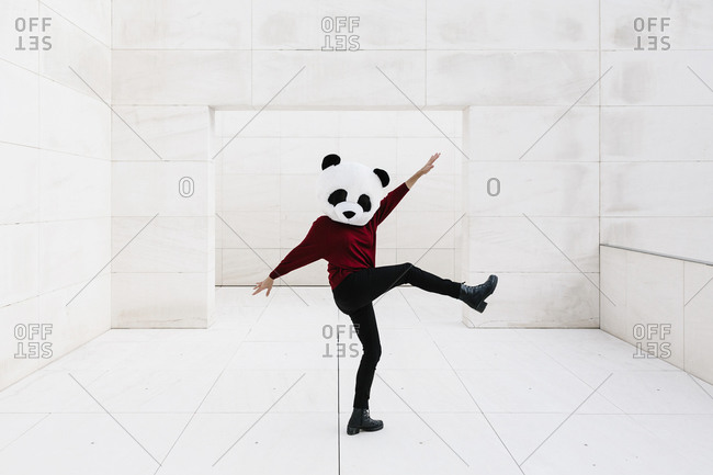 Woman doing with leg up wearing panda mask standing against doorway