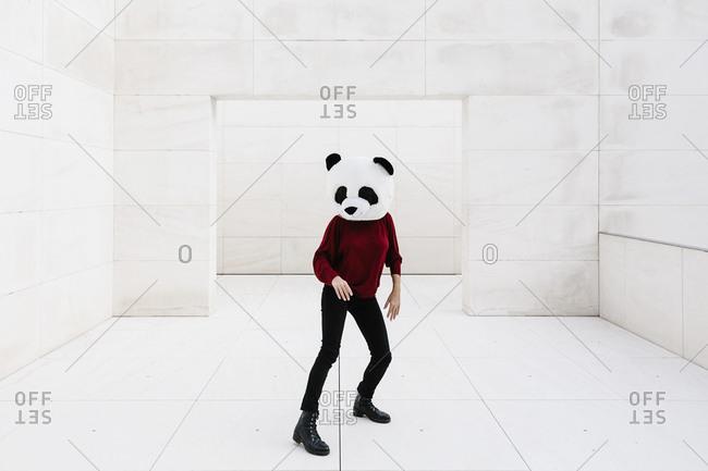 Woman wearing panda mask standing on tiled floor against doorway
