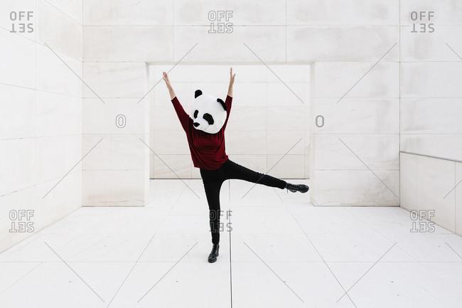 Woman wearing panda mask with arms raised standing against doorway