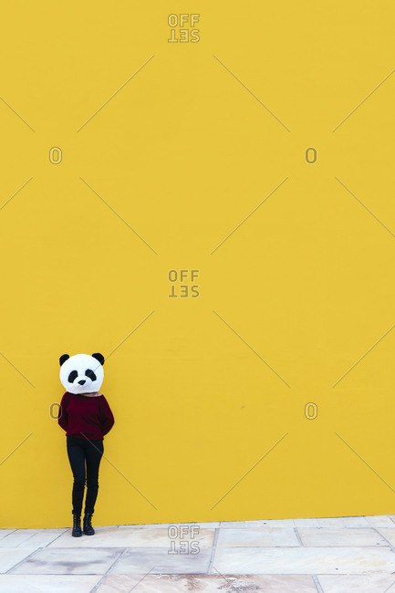 Female wearing panda mask while standing against yellow wall
