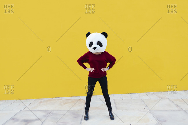 Woman with hand on hip wearing panda mask while standing against yellow wall