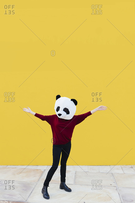 Woman with arms outstretched wearing panda mask while standing against yellow wall