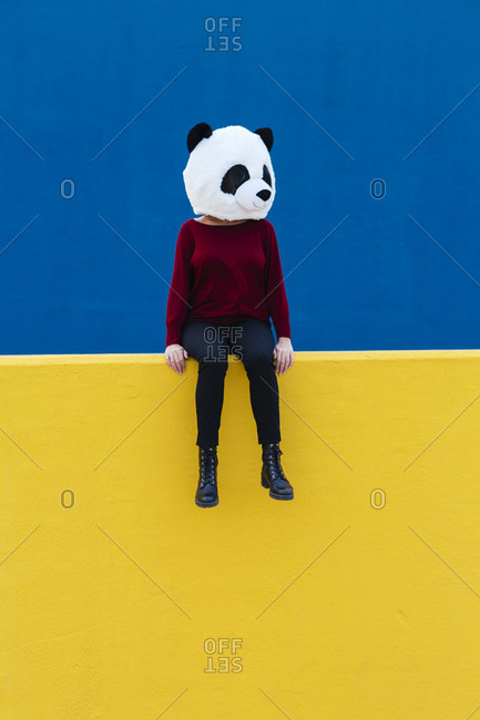 Woman in panda mask sitting on yellow retaining wall