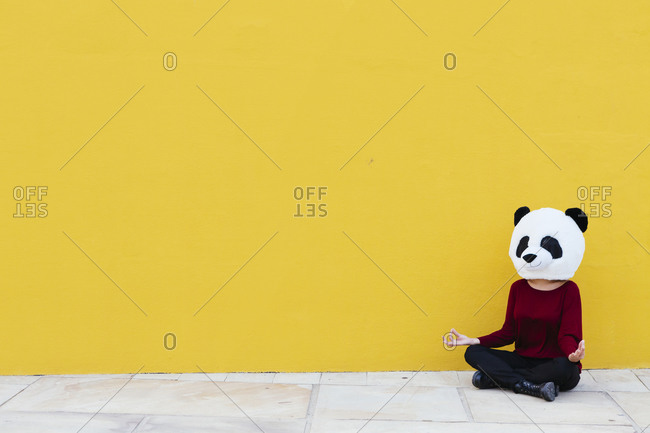 Woman wearing panda mask while sitting in lotus position against yellow wall