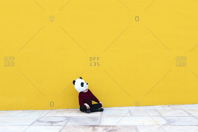 Woman wearing panda mask while sitting in cross-legged against yellow wall