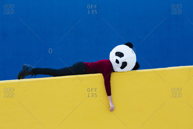 Female wearing panda mask while lying on yellow retaining wall