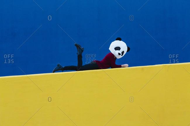 Woman wearing panda mask while lying down on yellow wall