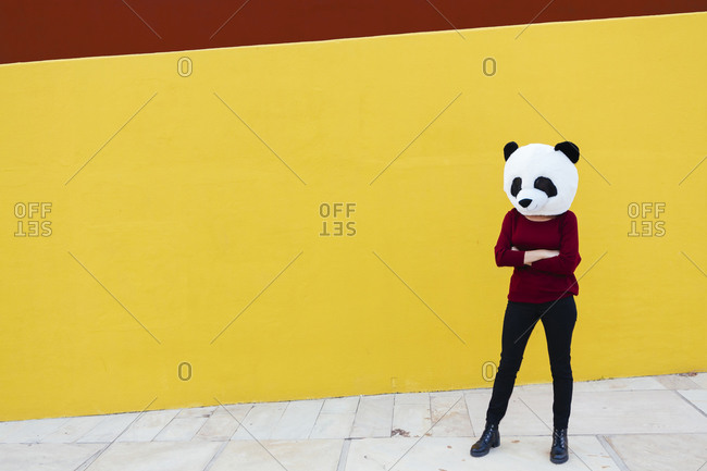 Woman with arms crossed wearing panda mask while standing against yellow wall