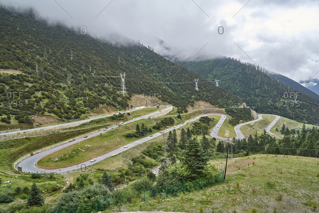 "Chengdu-Lhasa Highway, Sichuan, China; August 5, 2019;  The ""Nu Jiang 72 Turns"" is one of the most famous sections of the winding road along the Sichuan-Tibet Highway. The stunning sight is between the counties of Basu and Bangda. Drivers, passengers, and even thrill-seeking cyclists ascend from 3,100 meters to a breathtaking altitude of 4,658 meters to feast their eyes. Viewing the spectacular hairpin bends of the ""Nu Jiang 72 Turns"" from above, one can see the meandering road winding against snow-crested mountains' backdrop."