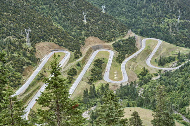 "Chengdu-Lhasa Highway, Sichuan, China; August 9, 2019;  The ""Nu Jiang 72 Turns"" is one of the most famous sections of the winding road along the Sichuan-Tibet Highway. The stunning sight is between the counties of Basu and Bangda. Drivers, passengers, and even thrill-seeking cyclists ascend from 3,100 meters to a breathtaking altitude of 4,658 meters to feast their eyes. Viewing the spectacular hairpin bends of the ""Nu Jiang 72 Turns"" from above, one can see the meandering road winding against snow-crested mountains' backdrop."