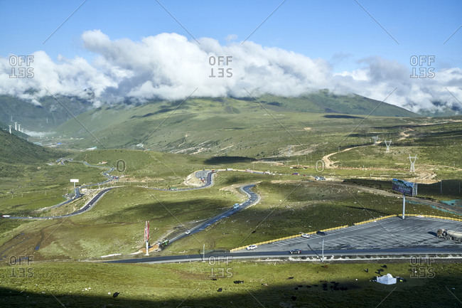 "Chengdu-Lhasa Highway, Sichuan, China; August 10, 2019;  The ""Nu Jiang 72 Turns"" is one of the most famous sections of the winding road along the Sichuan-Tibet Highway. The stunning sight is between the counties of Basu and Bangda. Drivers, passengers, and even thrill-seeking cyclists ascend from 3,100 meters to a breathtaking altitude of 4,658 meters to feast their eyes. Viewing the spectacular hairpin bends of the ""Nu Jiang 72 Turns"" from above, one can see the meandering road winding against snow-crested mountains' backdrop."