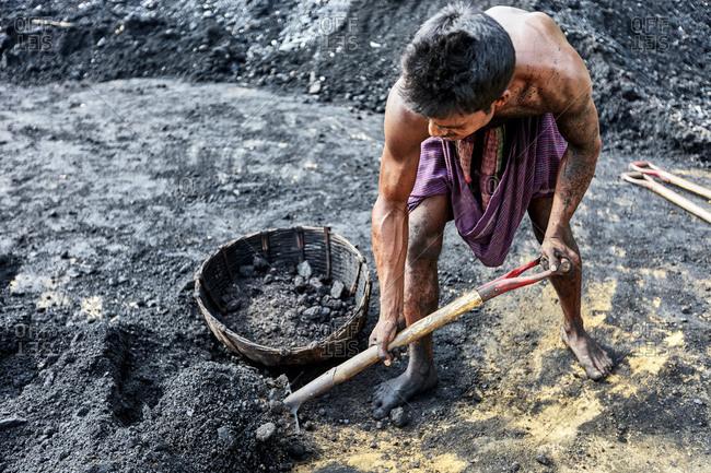 May 14, 2013: Barisal, Bangladesh;  A laborer filling up a basket with coal at a river bank in Bangladesh