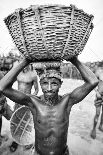 May 14, 2013: Barisal, Bangladesh; Close-up of low-income laborer carrying coal on his head at a river bank in Bangladesh