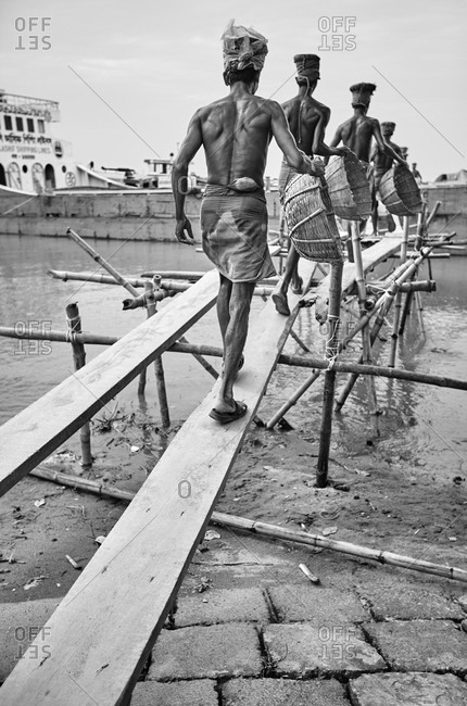 May 14, 2013: Barisal, Bangladesh; Low-income laborers are carrying coal unloaded from a cargo ship on the head at a river bank in rural Bangladesh; Black and white photography