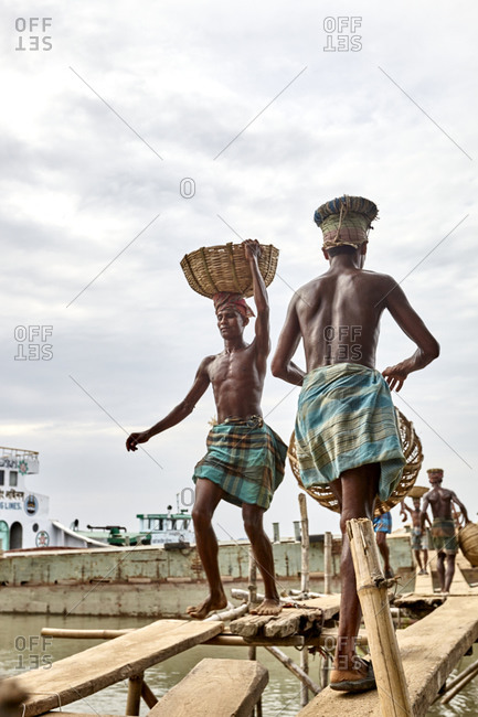 May 14, 2013: Barisal, Bangladesh; Low-income laborers are carrying coal unloaded from a cargo ship on the head at a river bank in rural Bangladesh