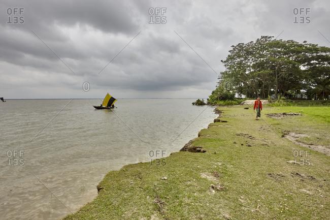 May 14, 2013: East Side of Kirtonkhola River, Barisal, Bangladesh, May 14, 2013; A man walking alongside Kirtonkhola River in Bangladesh