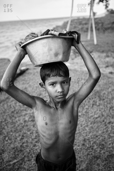 May 14, 2013: East Side of Kirtonkhola River, Barisal, Bangladesh, May 14, 2013; Portrait of a boy from a fishing village on the shore of Kirtonkhola River in Bangladesh; Black and white photography