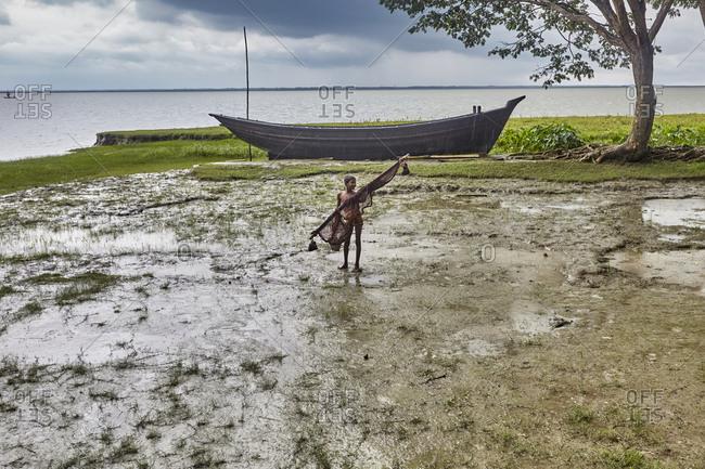 May 14, 2013: East Side of Kirtonkhola River, Barisal, Bangladesh, May 14, 2013; A boy holding fishing net on the shore of Kirtonkhola River in Bangladesh during rainfall