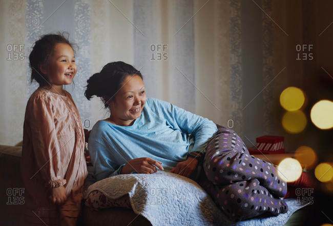 Mother and daughter watching TV at home decorated for Christmas holiday