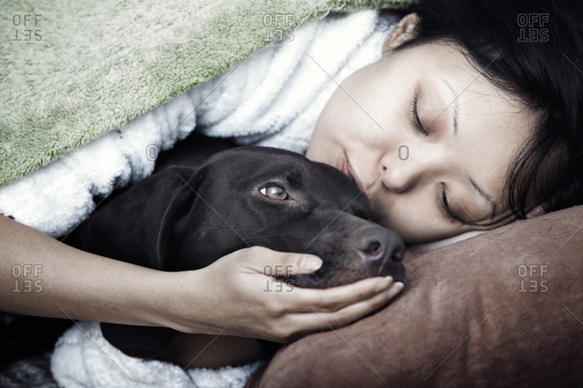 Woman laying together with her dog and hugging