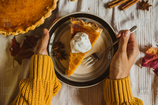 Overhead view of a woman eating a slice of pumpkin pie