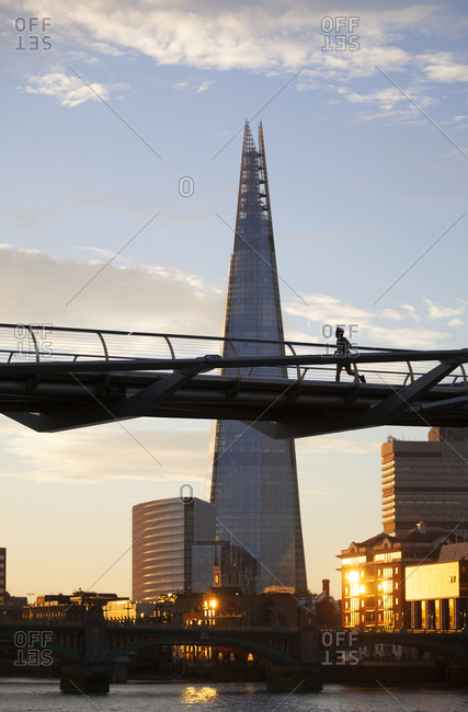 London, United Kingdom - September 11, 2016: Jogger on the Millennium Bridge at sunrise above the River Thames with the Shard office tower in the background