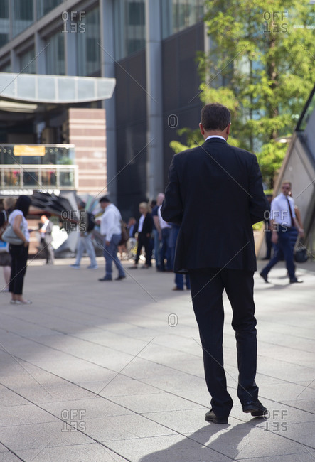 Rear view of an executive businessman walking at the Canary Wharf business district