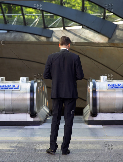 Rear view of businessman looking away at his smart phone as he enters the Canary Wharf Underground Station in London, England
