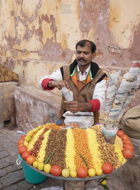 Jaipur, Rajasthan, India - January 5, 2020: Street food vendor selling lentils in paper cones