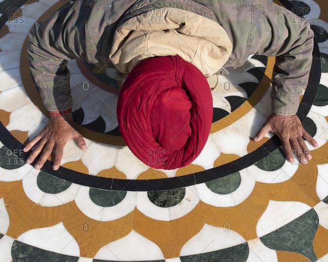 Overhead view of a worshipper kissing the threshold at the Sri Harmandir Sahib temple in Amritsar, India