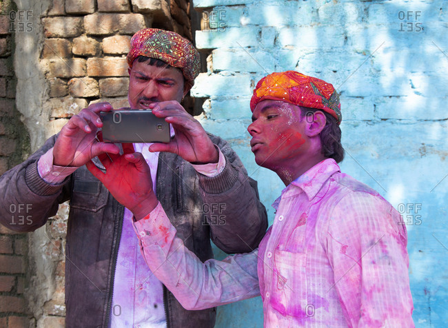 Mathura, India - March 5, 2015: Two men taking photos with smart phone during Holi Festival of Color