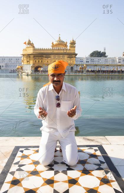 Amritsar, India - January 6, 2020: Worshipper kneeling at the Sri Harmandir Sahib temple