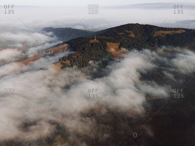 Aerial view over low lying clouds surrounding mountains with dense forest
