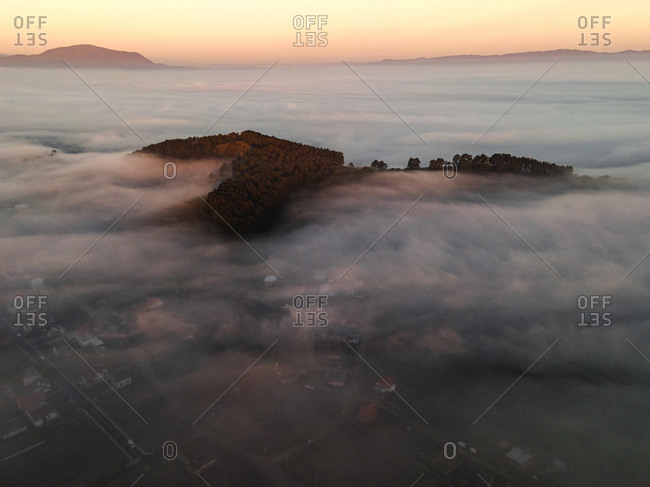 Fog covering vast landscape with mountains homes at sunrise