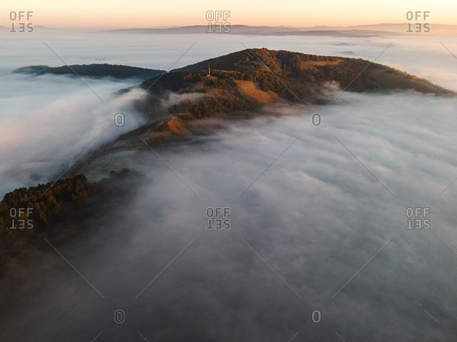 Low lying clouds surrounding mountains with dense forest at sunrise