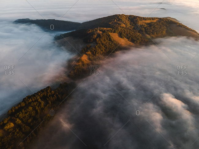 Drone shot over dense fog surrounding mountains with lush forest at sunrise