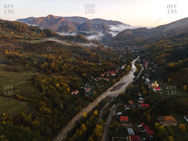 Bird's eye view over river running through mountainside homes
