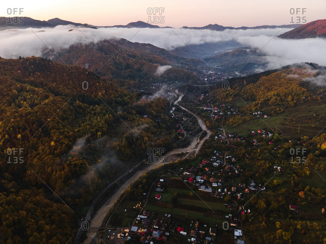 Aerial view over river running through mountainside village
