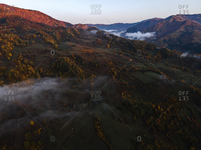 Bird's eye view over patchy fog in the mountains at sunrise