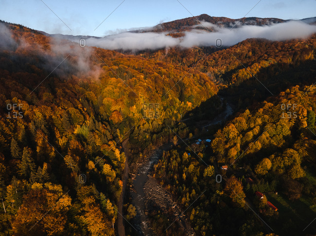 Bird's eye view over river and beautiful fall foliage in the mountains