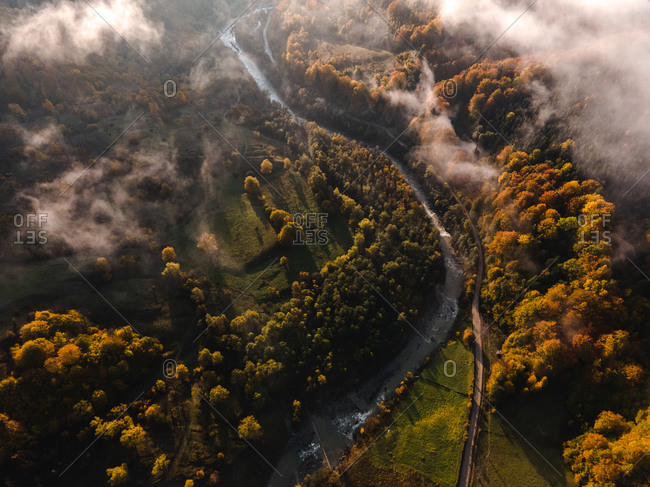 Drone shot of fall mountain landscape with winding river and patchy fog