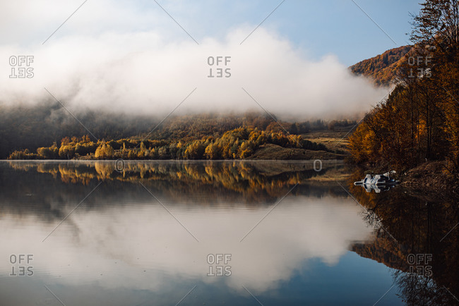 Mountainside lake reflecting fall forest and clouds