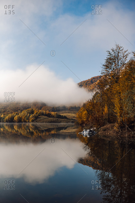 Mountainside lake reflecting a colorful autumn forest and clouds
