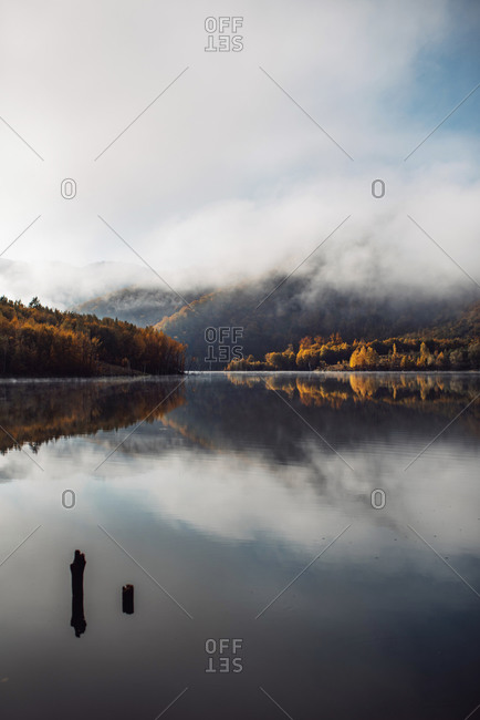 Dense clouds and autumn forest reflecting in a mountainside lake