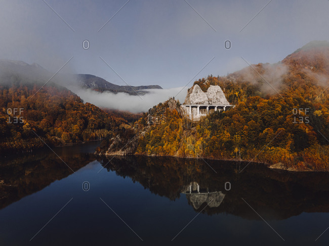 Fall foliage covering rocky mountainside lake with dense fog in the distance