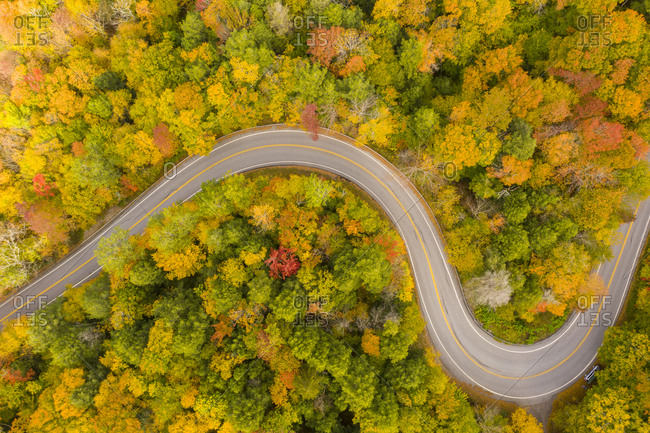 Drone show of winding road leading through fall foliage in New Haven, Vermont